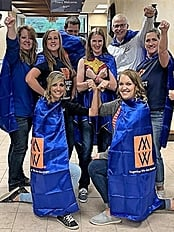 Minnwest team wearing capes and posing like super heros