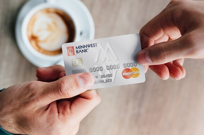 someone paying for coffee with Minnwest back debit card